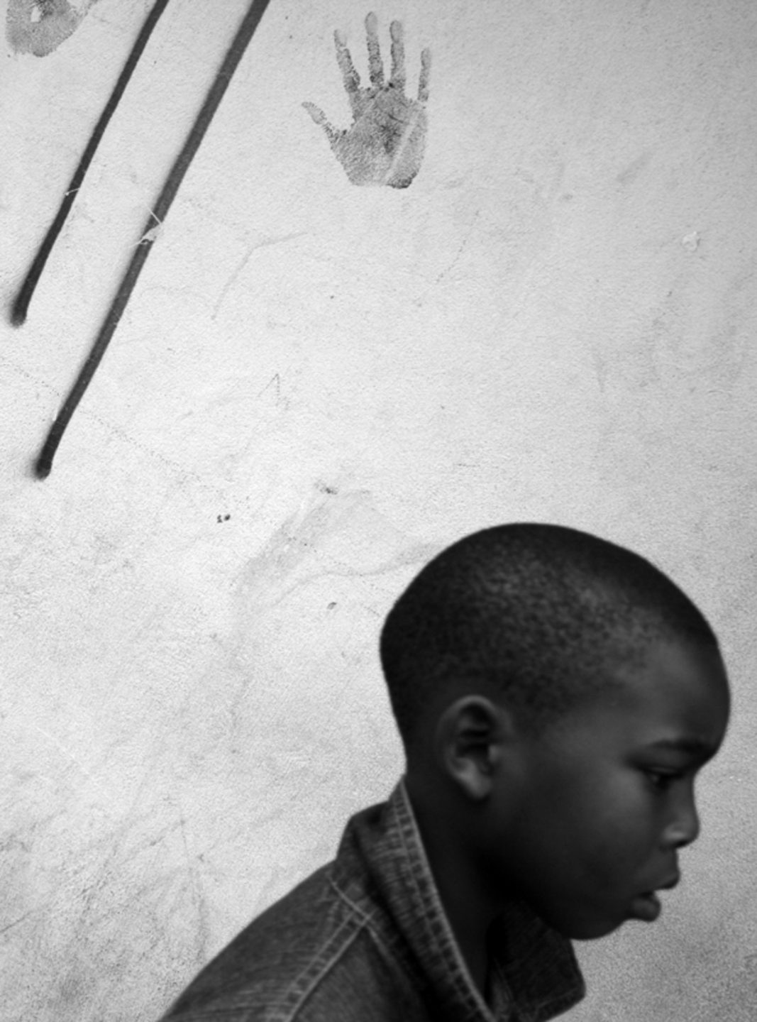 Boy walks past the mark of a hand printed on wall, 2012.